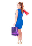 Young woman in blue dress with shopping bags Stock Photo