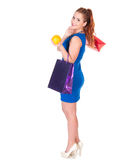 Young woman in blue dress with shopping bags and orange Royalty Free Stock Photo