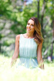 Young woman in blue dress sitting on grass Stock Photography