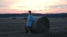 Young woman in a blue dress stands near haystack. stock video footage