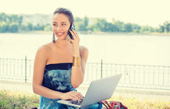 Young woman in blue dress talking on mobile phone outdoors Royalty Free Stock Photo