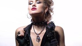 Young woman with blue eyes and blonde hair, posing and touching her spiked vest. Beautiful blonde woman in rocker clothes and leather gloves, posing in the stock video