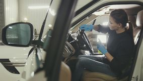 Young woman in blue gloves is cleaning interior of the car for luxury SUV. Close up royalty free stock photo