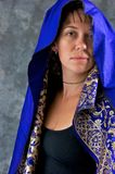 Young woman in blue and gold cape Royalty Free Stock Photo