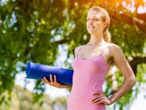 Young woman with a gym mat in the park Royalty Free Stock Images