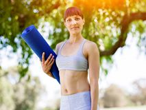 Young woman witth a gym mat in the park Royalty Free Stock Photo