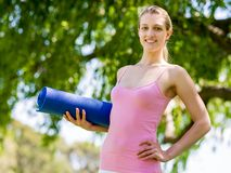 Young woman with a gym mat in the park Stock Images