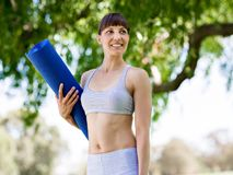 Young woman witth a gym mat in the park Royalty Free Stock Photos