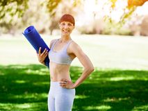 Young woman witth a gym mat in the park Stock Image