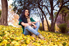 Young woman with blue hair sitting in park Stock Images