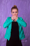 Young woman in blue jacket close the mouth with her hands Royalty Free Stock Image