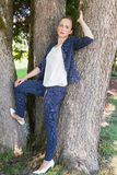 Young Woman in Blue Jacket Leaning Against Trees Stock Images