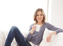 A young woman in blue jeans holding a white cup Stock Photos