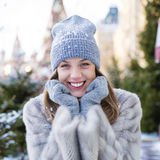 Young woman in a blue knitted hat and gray mink coat Stock Images