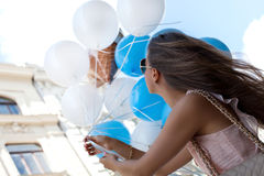 Young woman with blue latex balloons. Royalty Free Stock Photography