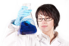 Young woman with blue liquid. A female scientific researcher looking at a liquid solution Royalty Free Stock Photo