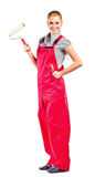 Young woman in blue overalls with painting tools Stock Photo