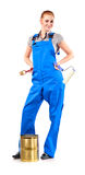 Young woman in blue overalls with painting tools Stock Image