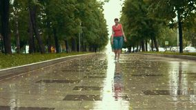28e7e3c33af8d7 A young woman in blue sandals walks by the wet path in the park during the