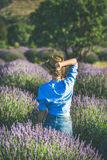 Young woman in blue shirt enjoying lavender field, Isparta, Turkey stock images
