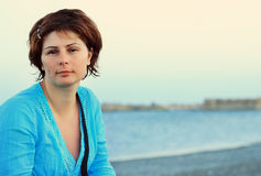 Young woman in blue shirt on a sea coast. Portrait of beautiful young woman in blue shirt on a sea coast, with space for text Royalty Free Stock Image