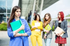 Young woman in a blue suit. Student with a folder. Education concept, exams, friendship and group of people royalty free stock images