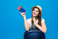 Young woman with blue suitcase and ticket passport on blue background. Young woman with suitcase and ticket on blue background Royalty Free Stock Photos