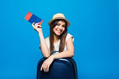 Young woman with blue suitcase and ticket passport on blue background. Young woman with suitcase and ticket on blue background Royalty Free Stock Photo
