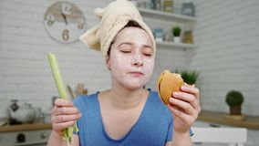 Girl with mask on face smells eats hamburger and celery. Young woman in blue t-shirt with mask on face and head wrapped in towel smells eats hamburger and celery stock video