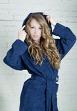 Young woman in blue terry robe looking at the camera Royalty Free Stock Image