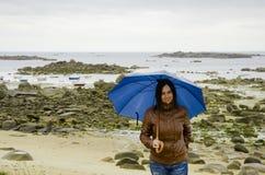 Young woman with blue umbrella Stock Photos