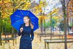 Young woman with blue umbrella in the Luxembourg garden of Paris on a fall or spring rainy day royalty free stock image