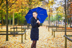 Young woman with blue umbrella in the Luxembourg garden of Paris on a fall or spring rainy day Royalty Free Stock Photos
