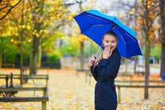 Young woman with blue umbrella in the Luxembourg garden of Paris on a fall or spring rainy day Royalty Free Stock Photography