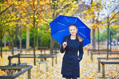 Young woman with blue umbrella in the Luxembourg garden of Paris on a fall or spring rainy day stock images