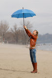 The young  woman with blue umbrella on windy day Stock Photo