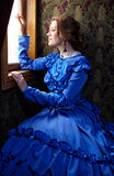 Young woman in blue vintage dress looking out the window in coup Stock Photo
