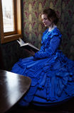 Young woman in blue vintage dress reading the book in coupe of r Stock Image