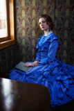 Young woman in blue vintage dress  sitting with book in coupe of Royalty Free Stock Photography