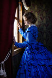 Young woman in blue vintage dress standing near window in coupe. Young woman in blue vintage dress late 19th century standing near window in coupe of retro Stock Images