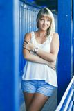 Young woman on blue wall background. Young blond woman posing on blue wall background Royalty Free Stock Photography