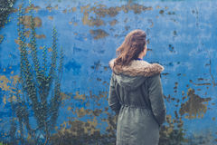 Young woman by blue wall on windy day Stock Photography