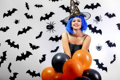 Young woman in a blue wig and witch`s hat black and orange balloons on a white background with black bats and spiders stock photos
