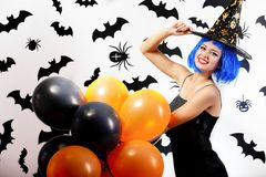 Young woman in a blue wig and witch`s hat black and orange balloons on a white background with black bats and spiders stock image