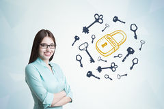 Young woman in blueish shirt, key and lock Royalty Free Stock Photos