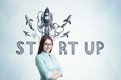 Young woman in blueish shirt, startup rocket Royalty Free Stock Photos