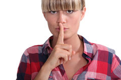 Young woman with a blunt fringe. Holding her finger to her lips royalty free stock photos