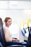 Young woman  on board of an airplane Stock Photo