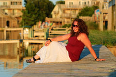 Young Woman Boardwalk NC Dock Summer Sunset. Beautiful redheaded plus-size woman sitting on the dock of the canal in Frisco, NC in the evening glow of sunset on royalty free stock photo