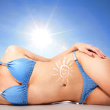 Young woman body at the beach with sun block cream. Attractive young woman body at the beach with sun shaped cream (sun block or sunscreen lotion ) over skin Stock Photo